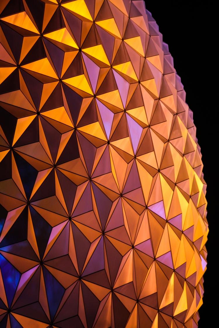 Disney World Epcot's Spaceship Earth glows with orange and yellow reflections at night NotSoSAHM