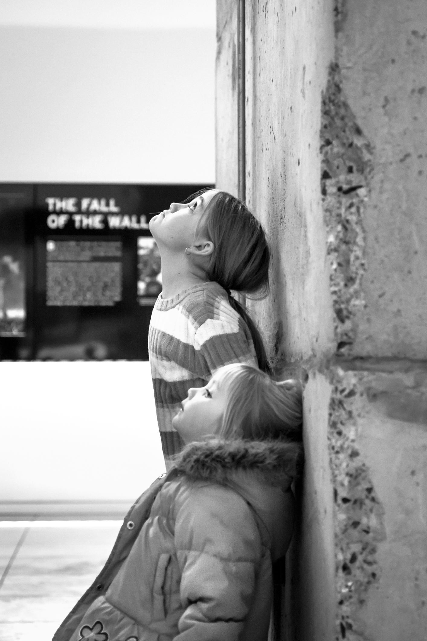 Two girls stand next to a wall possibly the Berlin Wall at the Newseum in Washington DC NotSoSAHM