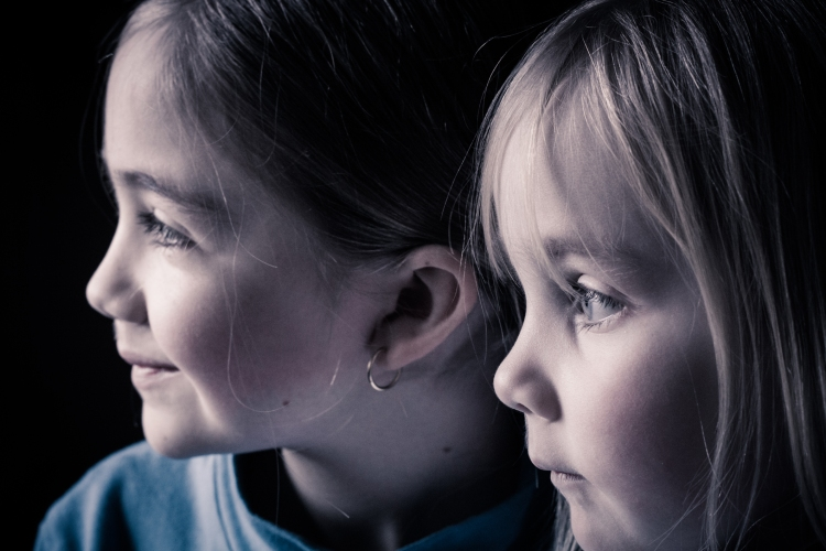 two sisters look out a window with light softly on their faces NotSoSAHM