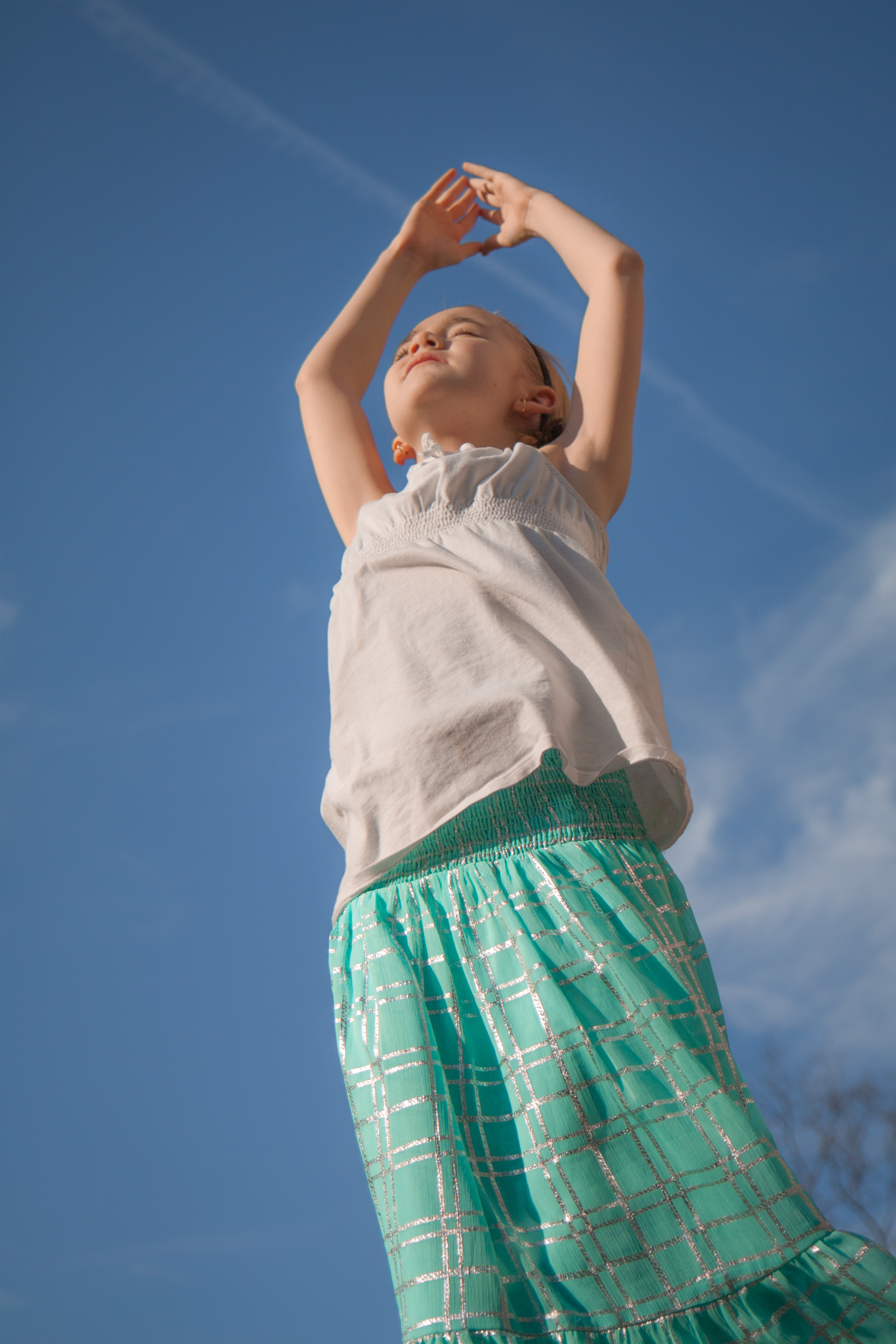 Girl soaks in the sun with hands raised above head NotSoSAHM