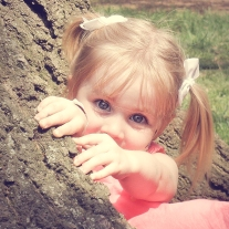 blue eyed girl looks out from behind a tree trunk NotSoSAHM