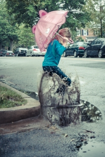 girl jumps in a puddle while holding an umbrella in the rain NotSoSAHM