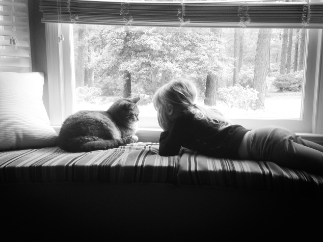 A girl talks to a cat in a window seat NotSoSAHM