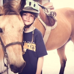 A girl stands with a horse in a barn NotSoSAHM