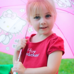 Girl looks out from under a pink umbrella Not So SAHM