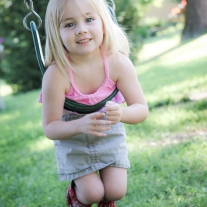 A girl in red boots plays in a swing Not So SAHM