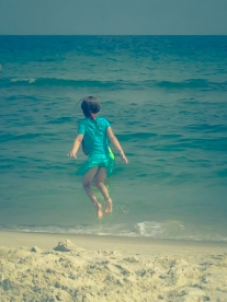 A girl jumps in anticipation as the ocean water creeps towards her feet Not So SAHM