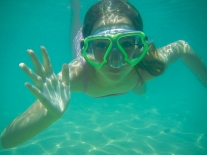 A girl waves to the camera underwater in Hawaii Not So SAHM