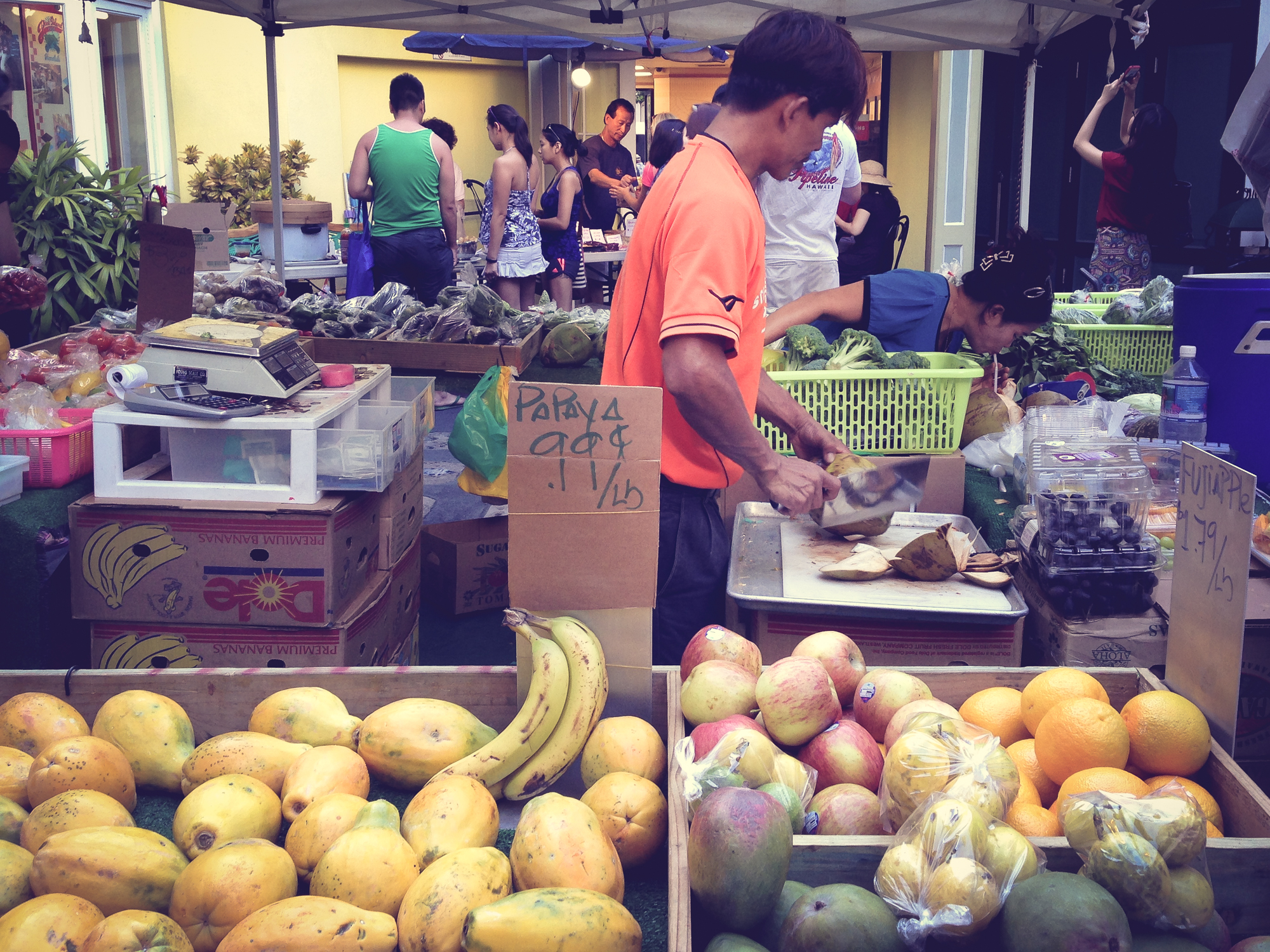A seller chops up fresh coconut at a fruit stand in Waikiki Hawaii Not So SAHM