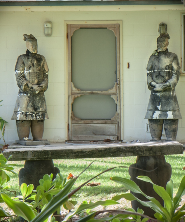 Two life-size asian statues stand on either side of a front door on a beach house on Oahu Not So SAHM