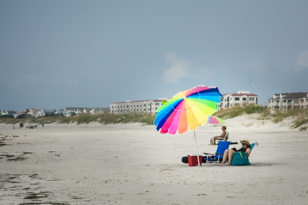 A woman sits shaded under a bright, colorful umbrella at Wrightsville Beach in North Carolina. Not So SAHM