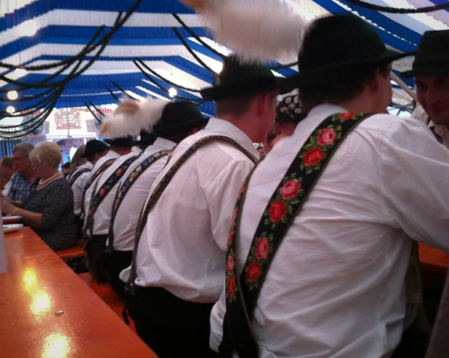 At least six young men sit side to side in a German fest tent, all wearing traditional suspenders. Not So SAHM