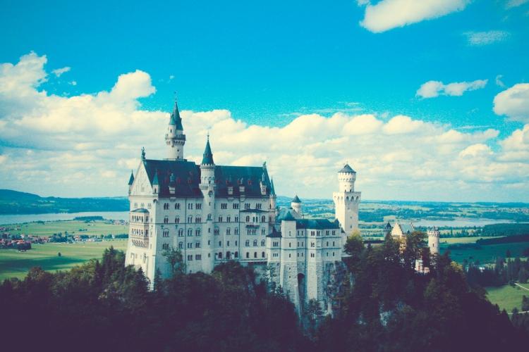 Schloss Neuschwanstein sits atop a hill with a bucolic backdrop. Not So SAHM