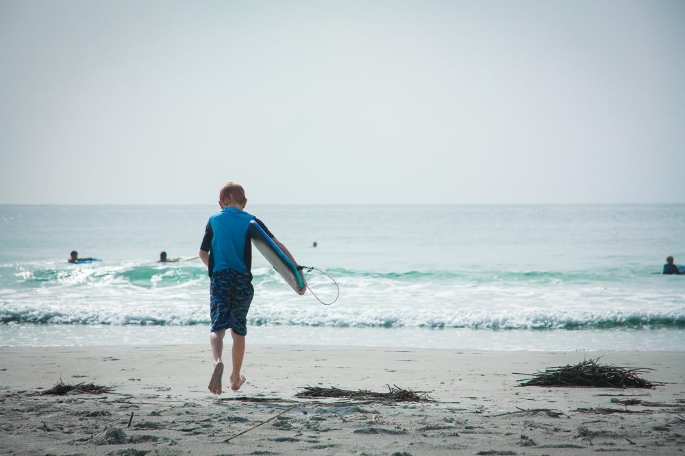A boy runs toward the surf with his boogie board. Not So SAHM