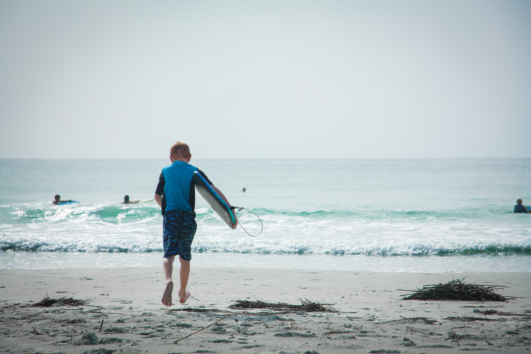 A boy runs toward the surf with his boogie board. Not So SAHM