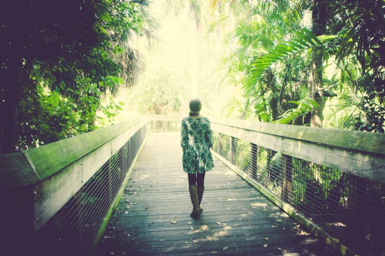Girl walks along a wooden walkway through lush landscape. NotSoSAHM
