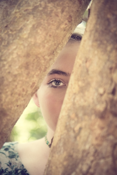 Girl peeks through trees and all you can see is one eye. Not So SAHM