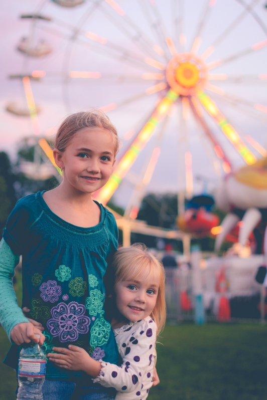 Two sisters hug at the fair in front of the ferris wheel. Not So SAHM