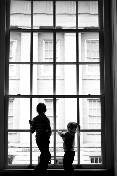 Two girls stand in silhouette in front of a tall museum window. Not So SAHM
