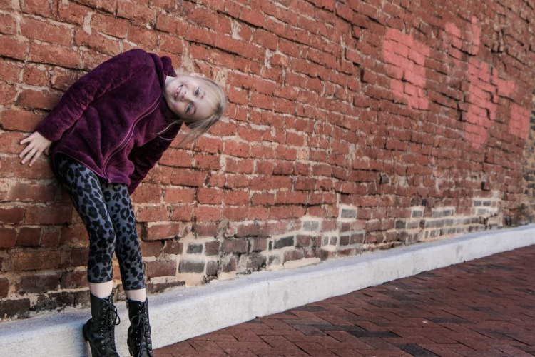 Girl stands in a silly pose in front of brick wall. Not So SAHM