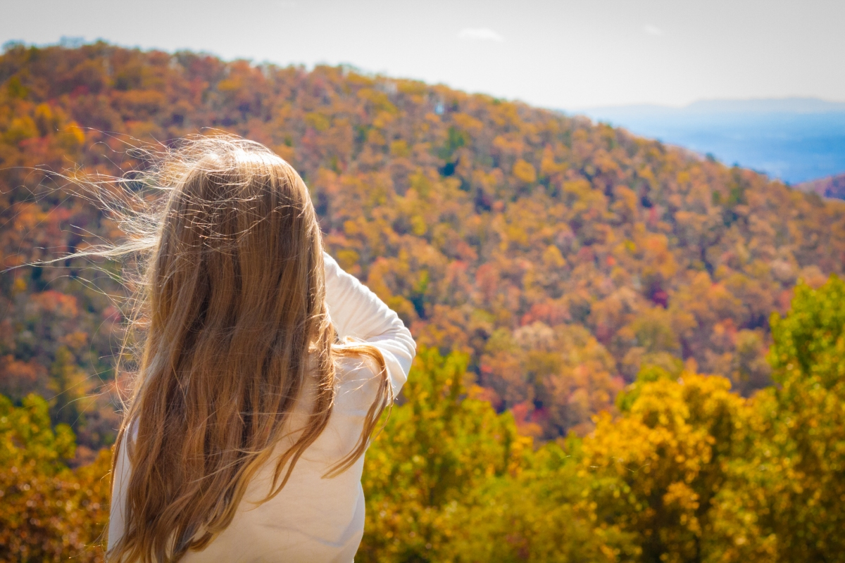 Girl looks out across the hills at all the turning fall leaves. Not So SAHM
