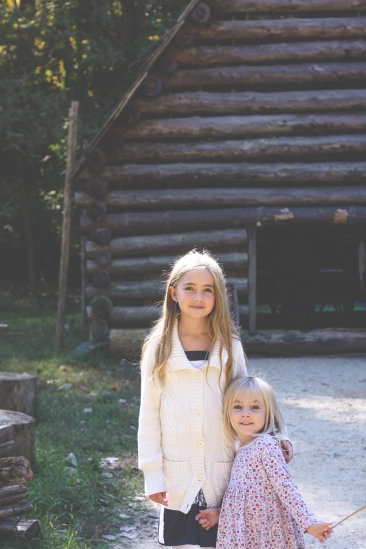 Two girls stand in front of a log barn on Claude Moore Colonial Farm. Not So SAHM