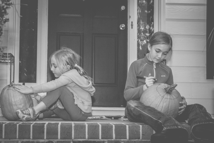 Two girls draw on pumpkins to be carved. Not So SAHM