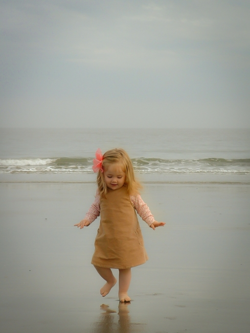 Little Girl looks at her reflection in the wet sand at the beach. Not So SAHM