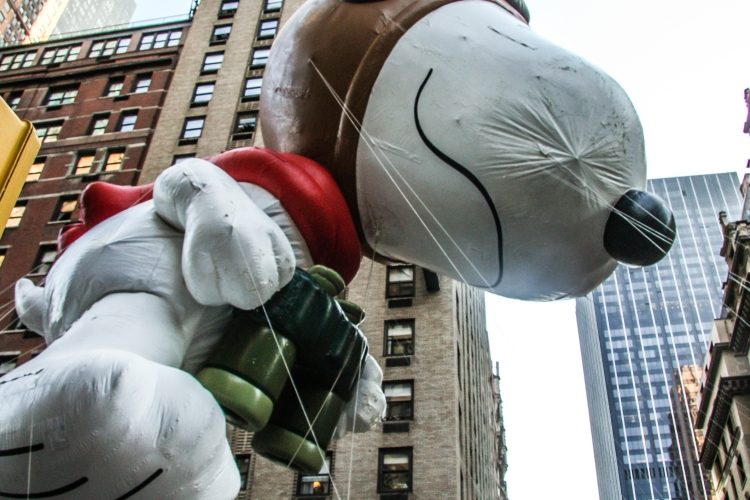 The snoopy balloon looms overhead on a new york street during the macy's thanksgiving day parade. Not So SAHM