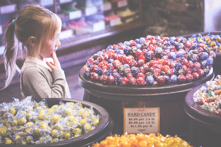 Girl stares at Tootsie Roll Pops in River Street Sweets in Savannah Georgia. Not So SAHM