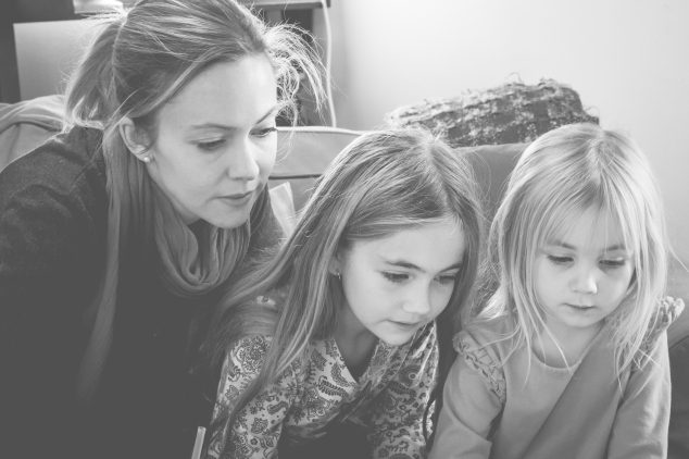Mom sits with her two daughters, all looking at a computer screen. Not So SAHM