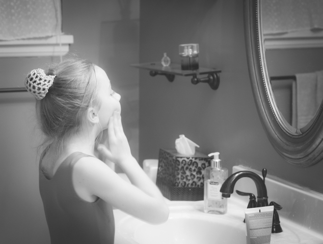 A young girl looks in the bathroom mirror as she washes her face. Not so SAHM