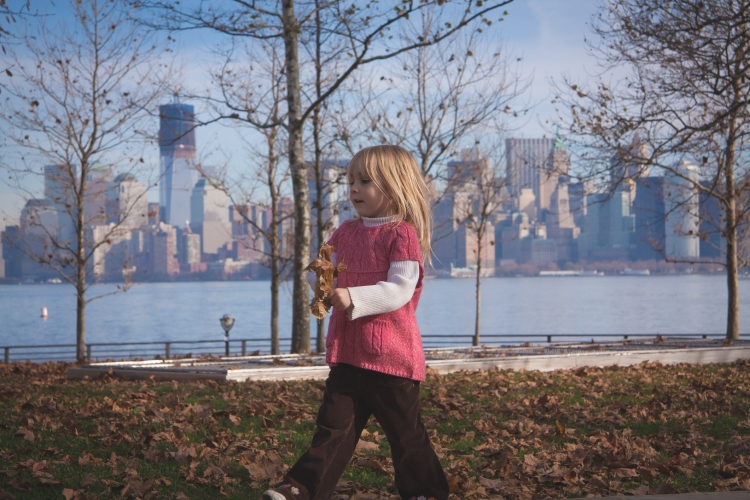 Girl walks with leaf with NYC skyline in background. Not So SAHM