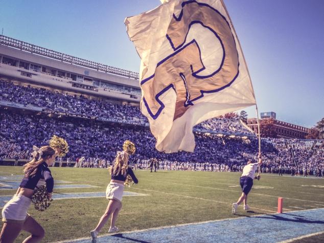 A cheerleader runs with the giant Ga Tech flag. Not So SAHM
