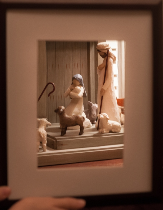 Nativity figures are shown behind a frame. Not So SAHM