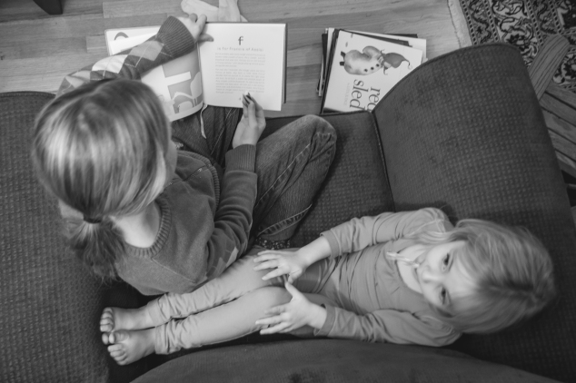 Older sister reads a Christmas story to younger sister. Not so SAHM