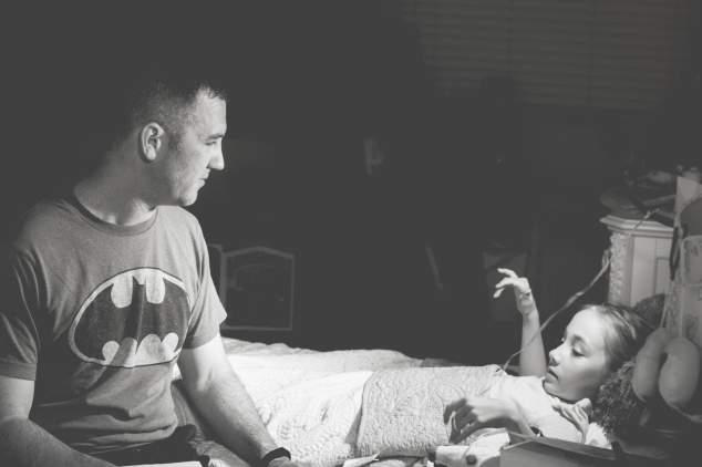 Dad talks with girl as he tucks her in at night. Photo by Not So SAHM