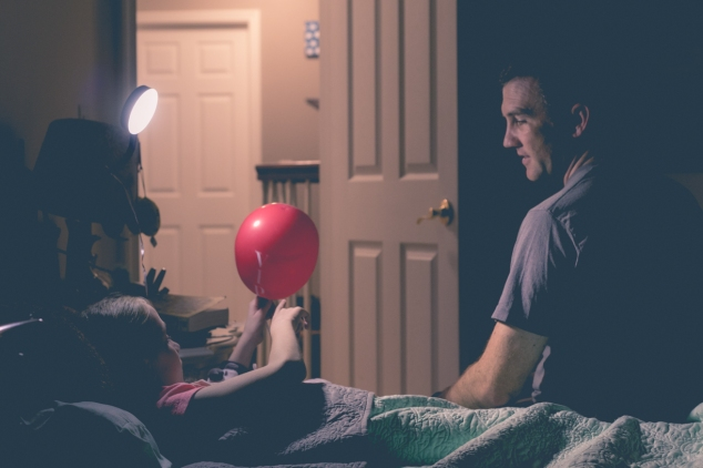 Dad talks with daughter as he tucks her in at night. Photo by Not So SAHM