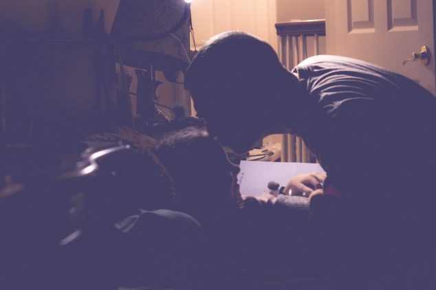 Dad kisses daughter on forehead while tucking her in at night. Photo by Not So SAHM