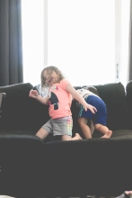 Two kids play and jump on the couch. Photo by VSD Photography